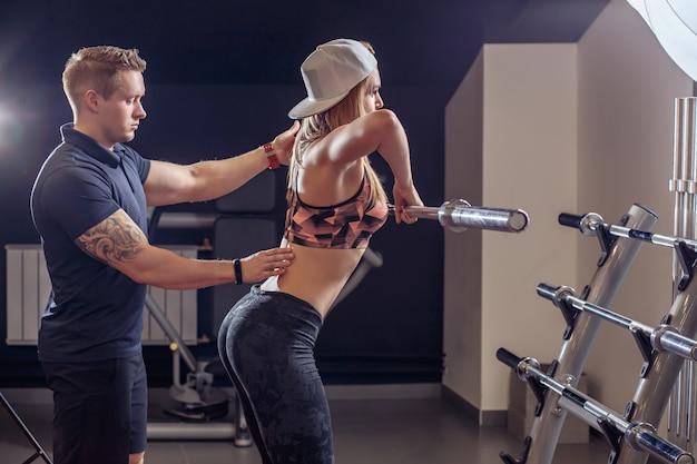 若い女性がジムでエクササイズ中にバーベルを持ち上げるのを助けるパーソナルトレーナー