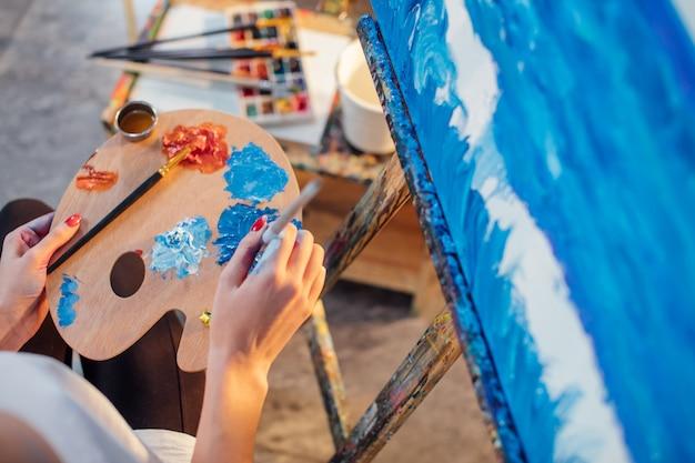 Художница смешивает цвета палитры в руке
