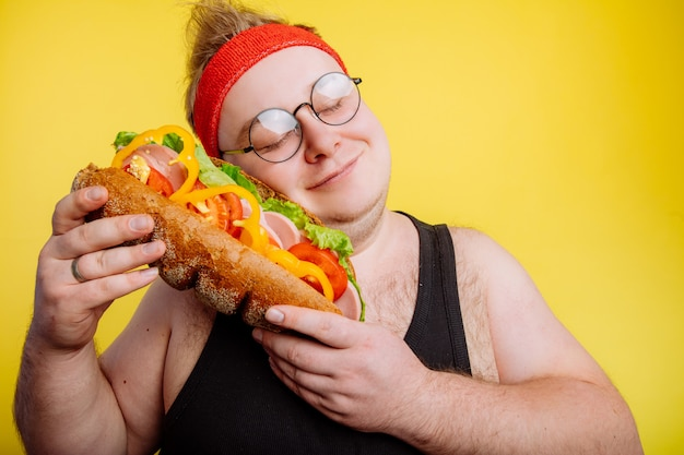 面白い男が巨大なハンバーガーを抱擁