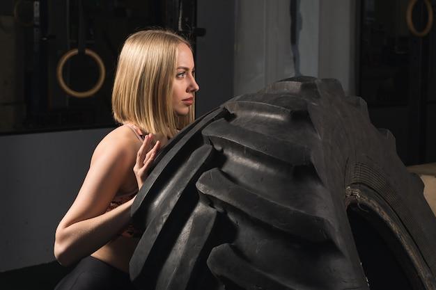 ジムでタイヤを押す強い女の子。