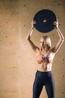 バーベルプレートは、ジムの運動でブロンドの女の子のトレーニングを上げる
