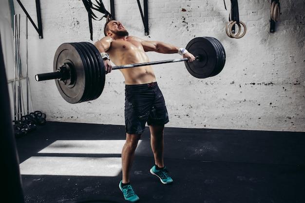 重りを持ち上げる男。バーベルで演習を行うジムで筋肉男のトレーニング