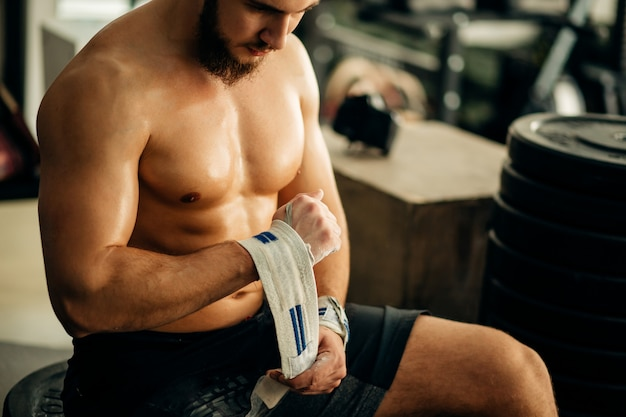 Мужчина готовится к тренировке, оборачивая ее руки повязкой