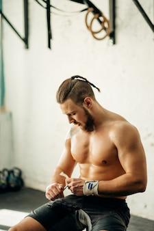 トレーニングの準備をしている男性、包帯テープで手を包んでいる男性