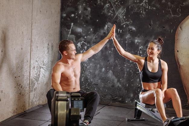 ローイングマシンで練習しながらハイタッチをしている男女