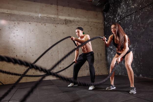 女と男のカップルが一緒にバトルロープトレーニングを行うトレーニング