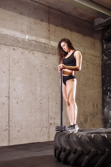 Женщина с молотком в тренажерном зале. девушка с кувалдой на тренировке