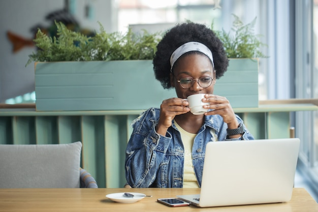 一杯のコーヒーを飲む若い女性
