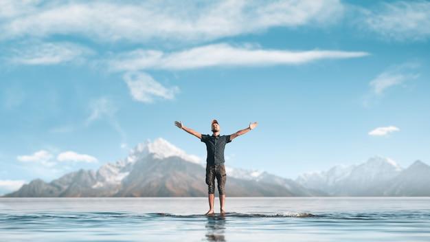 男は手を上げた。彼は山の湖に立っています。