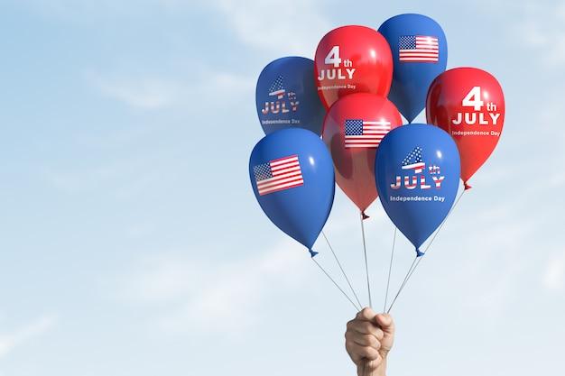 Рука держит воздушные шары, празднуя четвертое июля