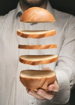 男性の手の上にパン片を浮上させる