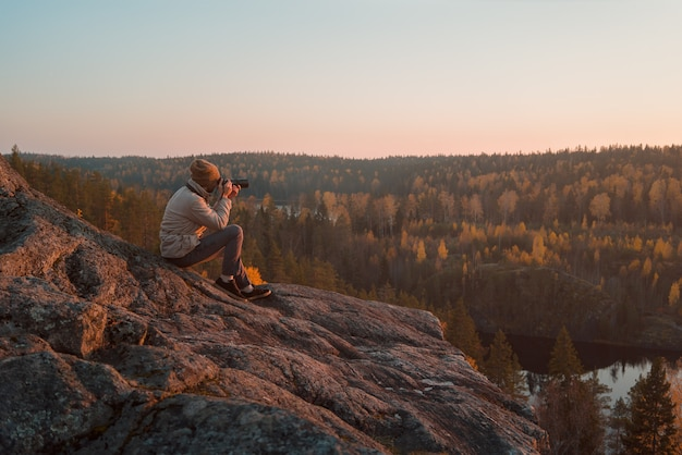 Фотограф на скале фотографирует осенний пейзаж.