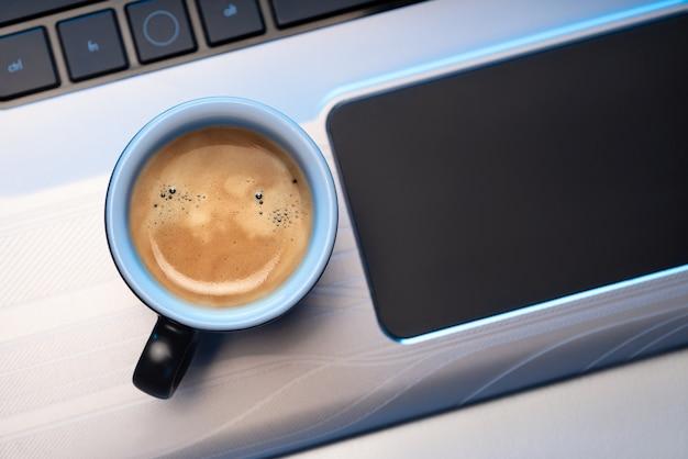 エスプレッソコーヒーマグカップはラップトップに立っています。