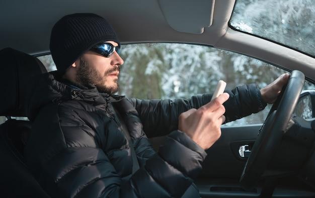 男は車を運転し、スマートフォンを使用しています。冬の外。