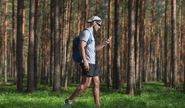 男は森の中を歩き、スマートフォンを使用します。