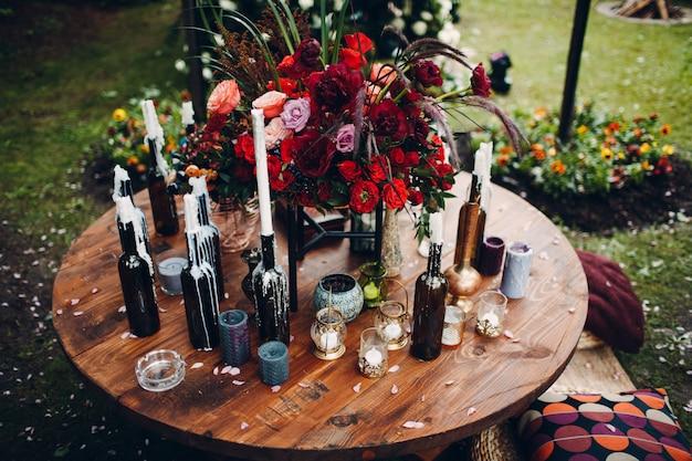 Стол, украшенный цветами и свечами в бутылке