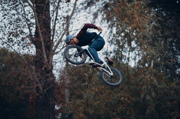 Профессиональный молодой спортсмен велосипедист с велосипедом в скейтпарк