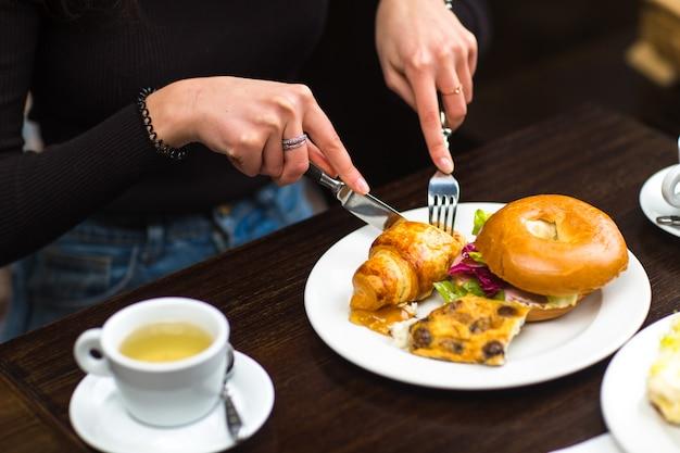 おいしいクロワッサンとパン屋さんのブリオッシュを食べる女性