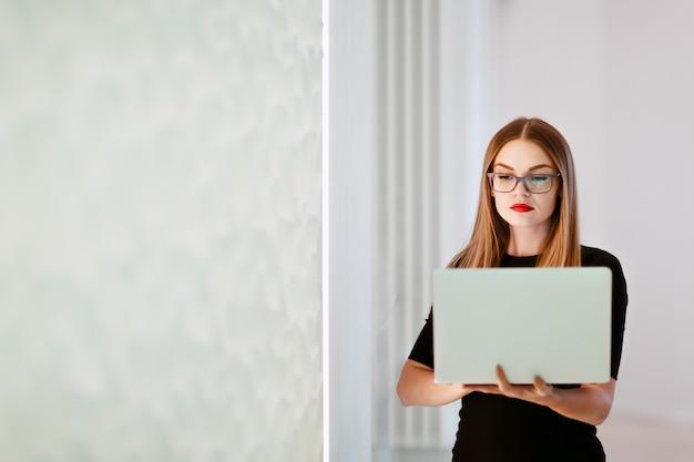 Деловая женщина в черном платье с ноутбуком