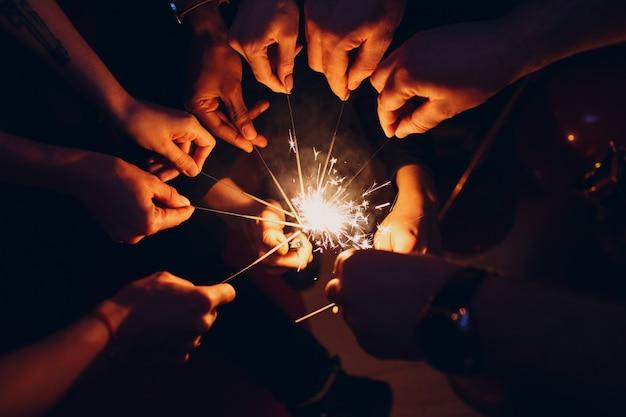 Люди поджигают бенгальские огни на вечеринке. вид сверху руки крупным планом.