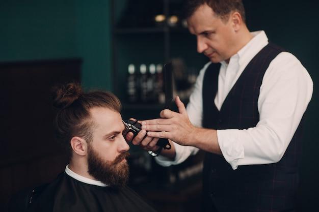 Парикмахерская с деревянным интерьером. бородатый образцовый человек и парикмахер.