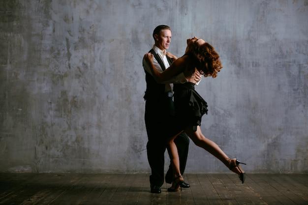 Молодая женщина в черном платье и мужчина танцуют танго