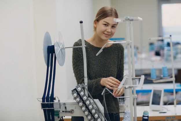 Молодая красивая швея шьет на швейной машине на фабрике