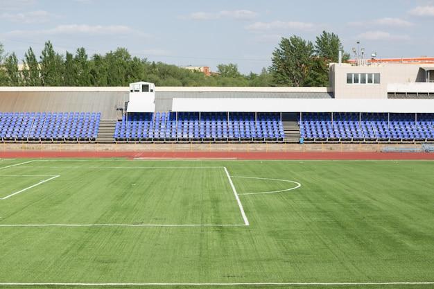 スタジアムでのサッカーのための緑の芝生のランニングトラックとフィールド
