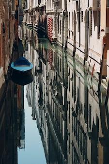 Лодка отражается на идеально гладкой поверхности канала в венеции