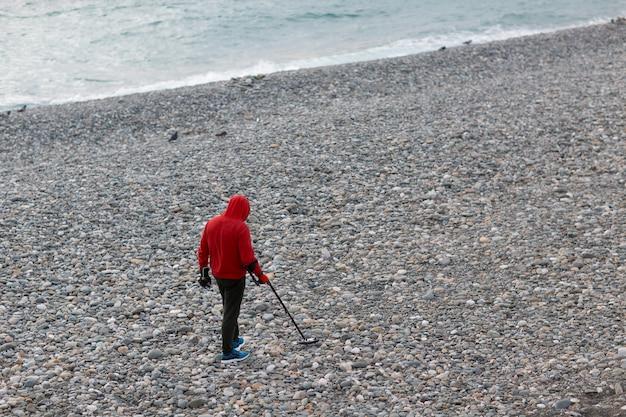 金属探知機を持つ男がビーチでコインやジュエリーを探しています