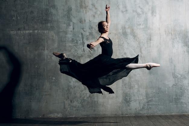 ジャンプ黒のドレスでバレエの女性ダンサー