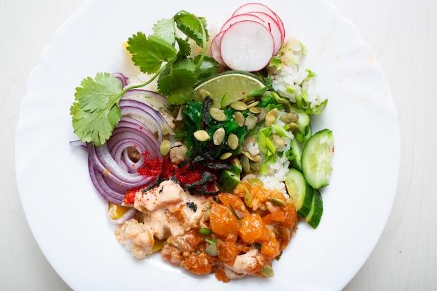 Тыкать с овощами, морепродуктами и лаймом на белой тарелке