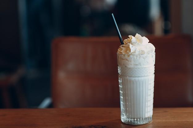 テーブルの上のガラスのコップにストローでバニラのミルクセーキ