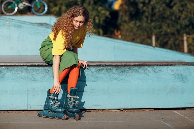 緑と黄色の服の若い女性のローラーはスケートを準備します