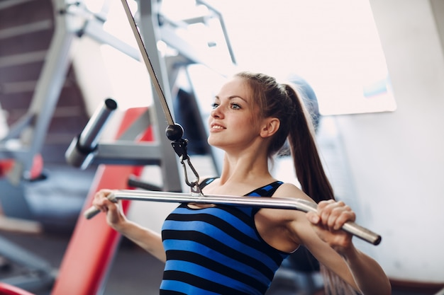 背中の筋肉をポンピングするためのマシンを使用して運動の女性