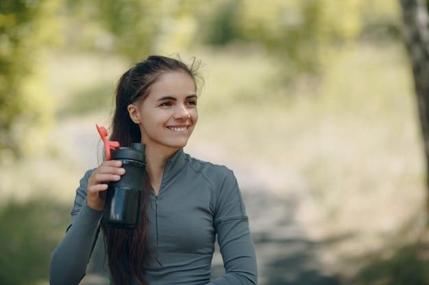 公園でジョギングした後笑顔の女性飲料水。