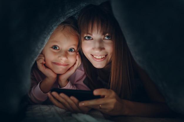 Молодая взрослая мать и дочь маленького ребенка, используя мобильный телефон вместе под одеялом