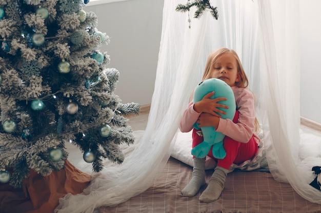 柔らかいおもちゃを自宅でクリスマスツリーの近くに座っている子供の女の子