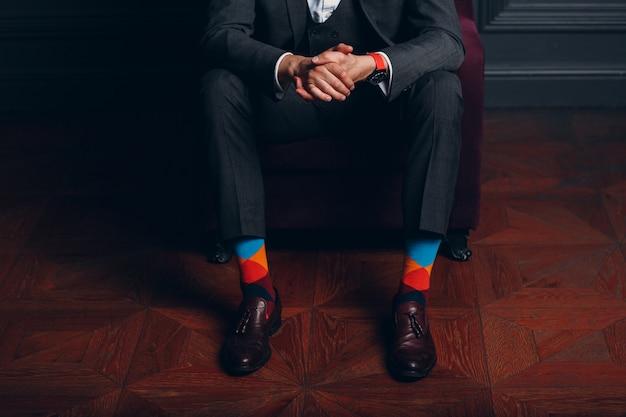 厳格なグレーのスーツとカラフルなマルチカラーの靴下のビジネスマン。ビジネスの男性と成功のコンセプト。