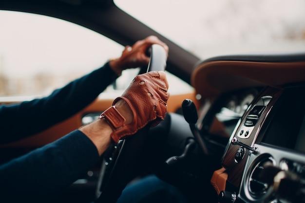 移動中の車を運転する革手袋のドライバーの手。