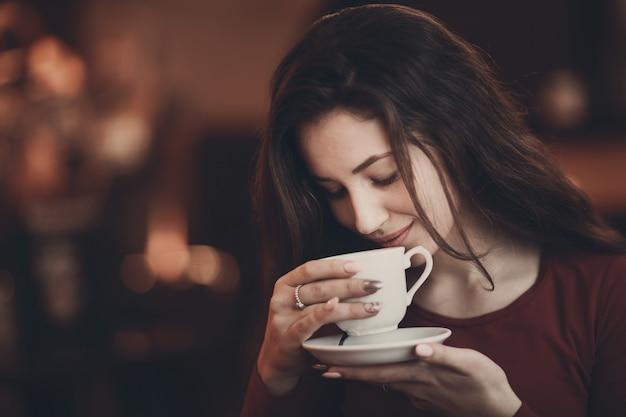Молодая красивая женщина пахнущий и пить кофе