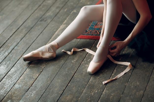 バレリーナはパフォーマンスに備える。プロの服、トウシューズ、黒のチュチュに身を包んだ若い美しい女性バレエダンサー。