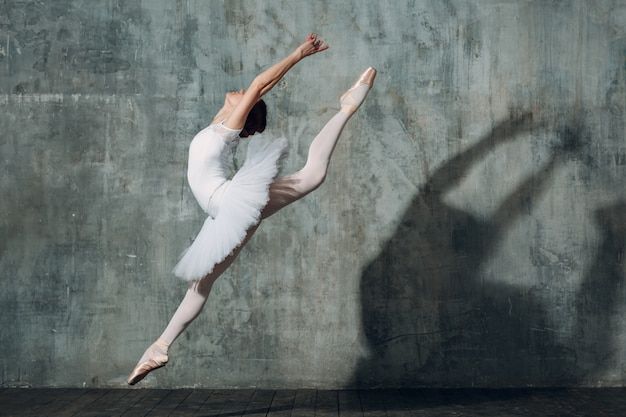 ジャンプバレリーナ。プロの服、トウシューズ、白いチュチュに身を包んだ若い美しい女性バレエダンサー。