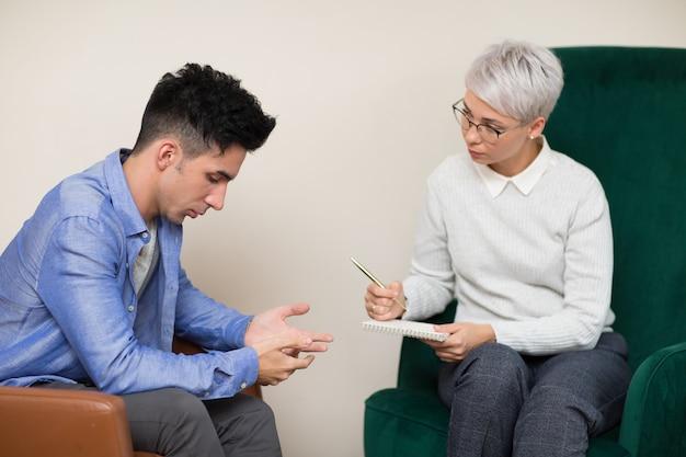 心理学者のためのレセプションで若い男性患者の相談。家族の問題