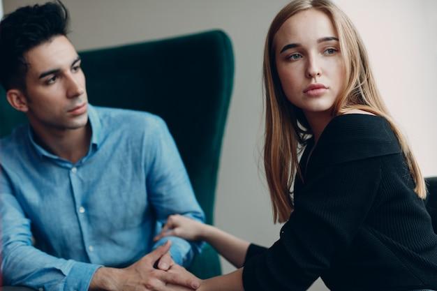 心理学者のためのレセプションでカップルの若い男性と女性患者の相談。家族の問題