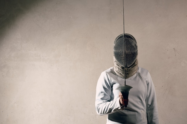 剣とマスクをフェンシングの剣士の女性