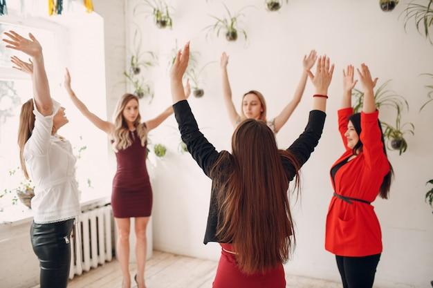 Женщины команды делают упражнения в офисе. гимнастика для женщин на работе. преимущества фитнеса и гимнастики для сотрудников и менеджеров.