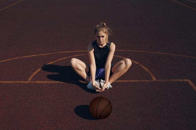 ストリートボールの試合前にウォーミングアップする若い女性のバスケットボール選手
