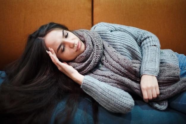 インフルエンザの風邪またはアレルギーの症状。組織にくしゃみをする発熱、アレルギー、スカーフが付いているベッドに横たわる一般的な風邪を伴う病気の若い女性。