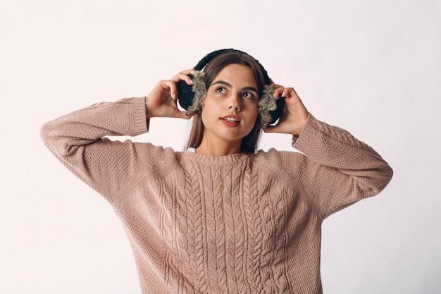 毛皮のヘッドフォンと分離されたセーターを保持している若いきれいな女性